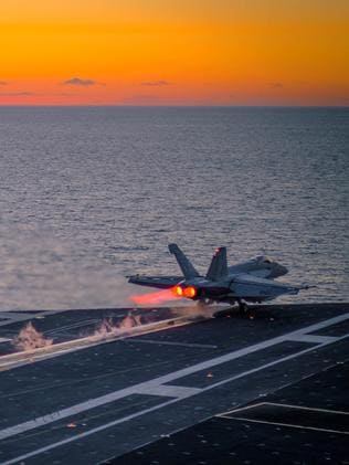 An F/A-18E Super Hornet launches at sunset from the flight deck of the aircraft carrier USS Ronald Reagan. The survivability of such aircraft in high-intensity warfare is in doubt. Picture: US Navy