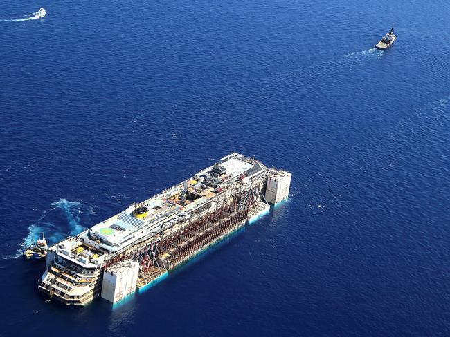 The wreck of the Costa Concordia is towed.