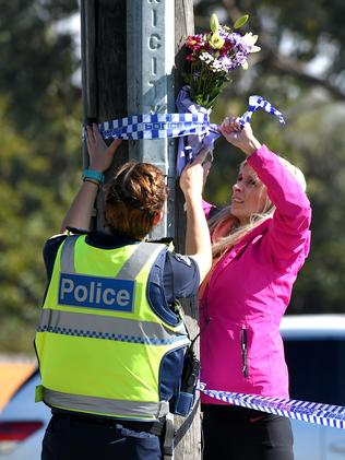 A police officer helps a woman lay some flowers at the scene. Picture: Nicole Garmston