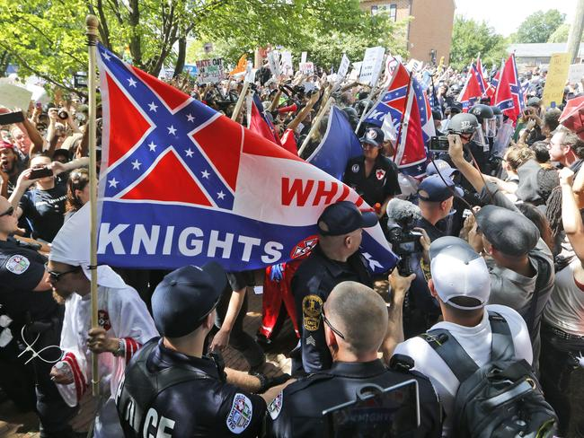 Members of the KKK escorted by police past a large group of protesters during a KKK rally in Charlottesville. Picture: AP