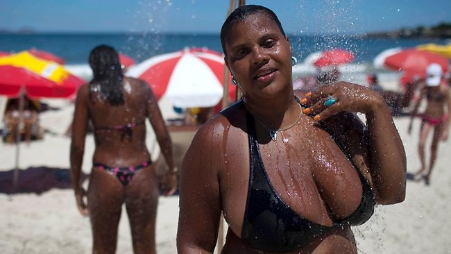 "Elisangela Inez Soares rinses off at a shower at Copacabana beach. ""Not everyone is built like a model,"" she says. Picture: AP"