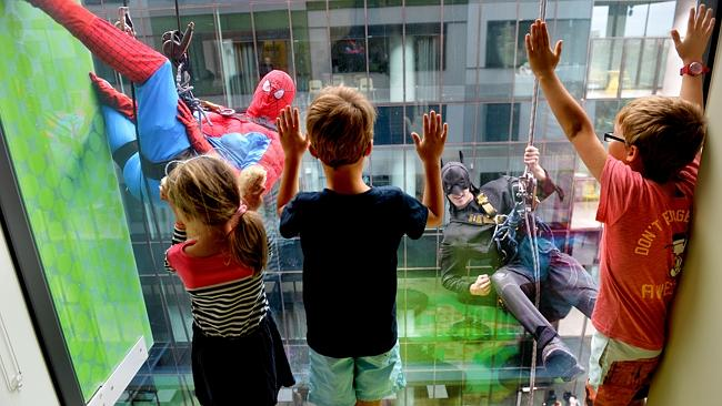 Batman (Blake Dawson) and Spiderman (Matthew Drape) from metropolitan Window Cleaning drop in to say hello to Lucie (4), Max and Charlie (both 7) Thompson at the RCH. Picture: Jay Town
