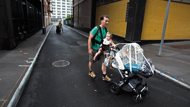 A man carries his daughter and pushes a stroller with his bird in a cage while evacuating lower Manhattan ahead of the arrival of Hurricane Irene. Picture: Chip Somodevilla / Getty /AFP