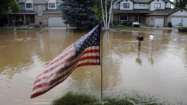 A muddy U.S. flag stands in front of flooded homes in Longmont, Colorado. Photo: AP