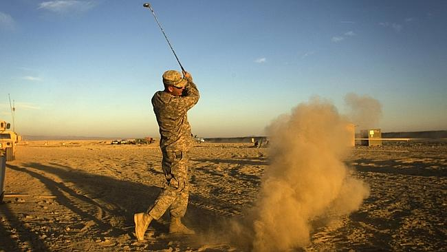 Ka-Boom ... A US Army soldier 333 Military Police Company hits a golf ball on his forward operating base in Paktika province,...
