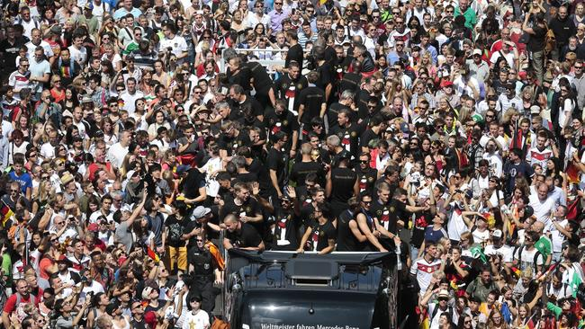 The German team celebrate on an open top bus on the way to the Brandenburg Gate in Berlin.