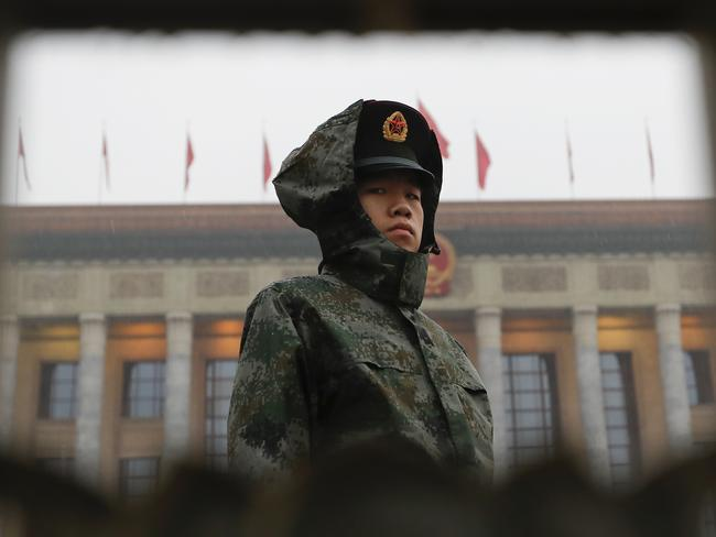 A solder in a raincoat stands watch outside the Great Hall of the People during the opening ceremony of the 19th Party Congress in Beijing. Picture: Andy Wong/AP
