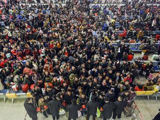 Railway workers hold back passengers at the Hankou Railway Station in Wuhan on the eve of the annual Spring Festival travel rush in central China's Hubei province on Thursday, Jan. 12, 2017. Officials expect that travelers will make almost 3 billion trips during the holiday travel rush that starts Friday and runs through Feb. 21. These trips include intercity flights, trains and local bus rides to villages. (Chinatopix Via AP)