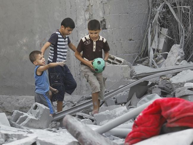Living in ruins ... Palestinian children inspect the wreckage of a building hit in an Israeli strike. Picture: Said Khatib