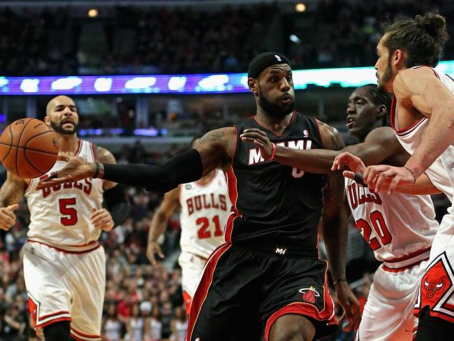 LeBron James #6 of the Miami Heat passes under pressure from Tony Snell #20 and Joakim No