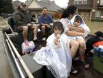 A family is evacuated from their home as floodwaters from Tropical Storm Harvey rise Monday, Aug. 28, 2017, in Spring, Texas. Picture: AP Photo/David J. Phillip