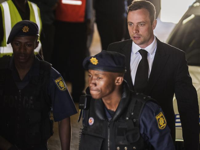 Straight to jail ... Oscar Pistorius is escorted to a police vehicle to be transported to prison following his sentencing at the High Court in Pretoria. Pic: AFP PHOTO/GIANLUIGI GUERCIA