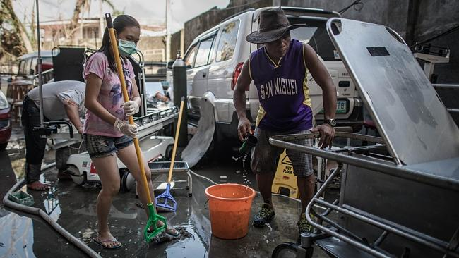 A man and woman wash hospital stretchers they retrieved from typhoon debris at the Divine Word hospital. Picture: Philippe Lopez