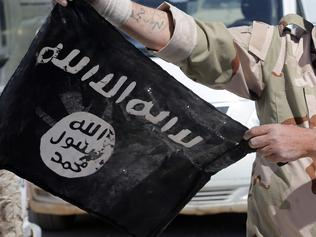 EDITORS NOTE: Graphic content / A Syrian soldier displays on April 4, 2016 an Islamic State (IS) group flag after Syrian troops regained control the previous day of al-Qaryatain, a town in the province of Homs in central Syria. IS jihadists withdrew from the town a week after the Russian-backed army and allied militia scored a major victory in the ancient city of Palmyra, which is also located in the vast province of Homs. The recapture of al-Qaryatain allows the army to secure its grip over Palmyra, where jihadists destroyed ancient temples during their 10-month rule and executed 280 people. / AFP PHOTO / JOSEPH EID