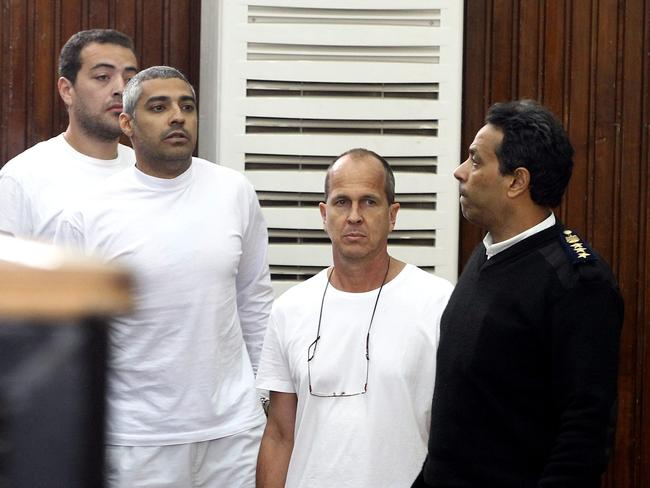 Outside their cages ... Australian journalist Peter Greste and other co-defendants are accompanied by a police officer outside court's cage during their trial for allegedly supporting a terrorist group and spreading false information, in Cairo, Egypt. Picture: KHALED ELFIQI