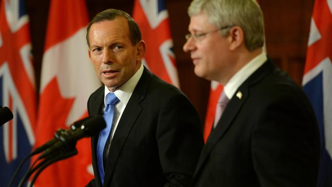 We stand together ... Tony Abbott and Canadian Prime Minister Stephen Harper speak at the press conference in Ottowa. Picture: Jake Nowakowski