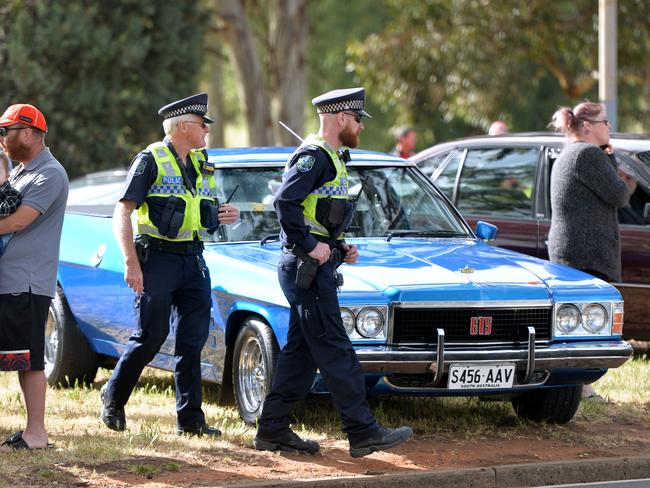 Police officers order cars to be removed from the median outside the Holden plant. Picture: AAP