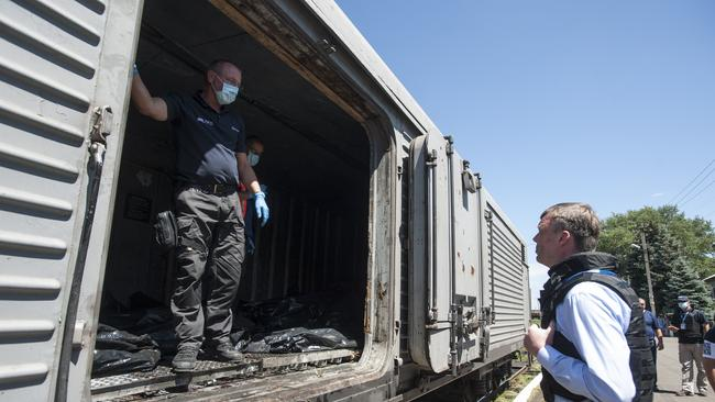 Deputy head of the OSCE mission to Ukraine Alexander Hug, right, speaks to a member of Netherlands' National Forensic Investigations team on the platform as a refrigerated train loaded with bodies / Picture: AP