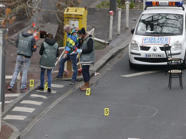 Police forensics experts examine the scene where a female police officer was shot dead in Montrouge, a southern suburb of Paris. Picture: Kenzo Triboiullard