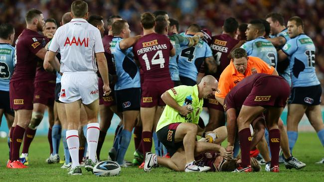 Brent Tate gets treatment after a tackle by Josh Reynolds and Beau Scott.