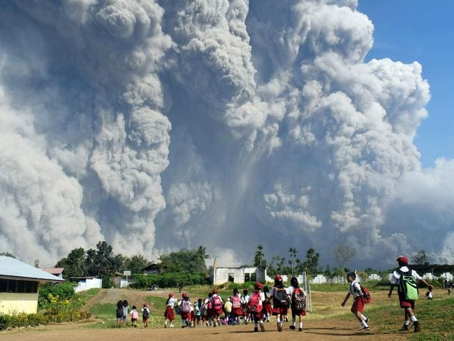 Schoolchildren run as Mount Sinabung unleashes its fury. Picture: Anto Sembiring / AFP