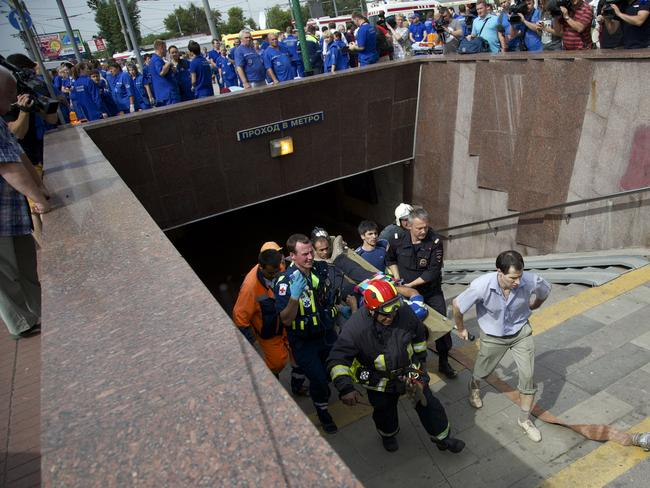 Day of mourning ... Paramedics and firefighters carry an injured man out of a subway station after a rush-hour subway train derailment in Moscow. Picture: AFP