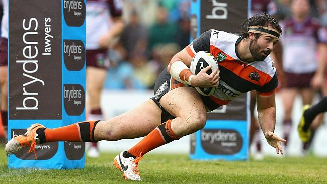 Aaron Woods of the Tigers scores a try.