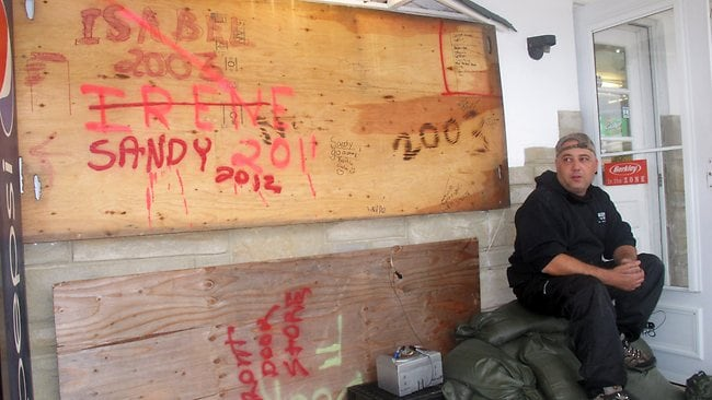 "Mark Palazzolo, owner of a bait and tackle shop on the Manasquan Inlet in Point Pleasant Beach, New Jersey, sits next to wood he has used to board up his business in previous major storms. He said, ""I think this is going to do us in."" Picture: Wayne Parry"