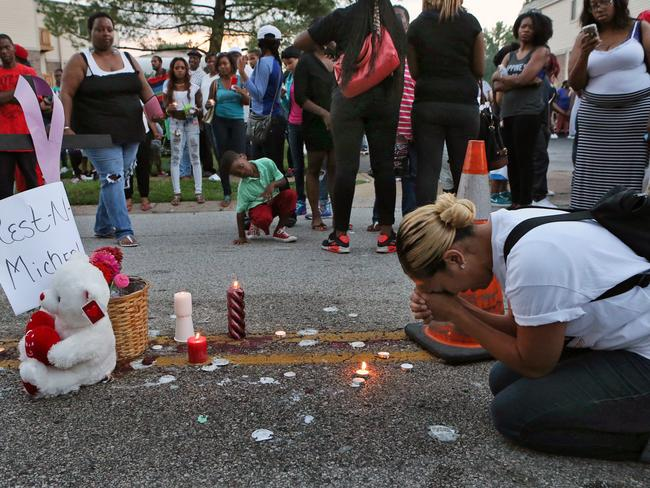 Meghan O'Donnell, 29, from St. Louis, prays at the spot where Michael Brown was killed. Pic: AP.