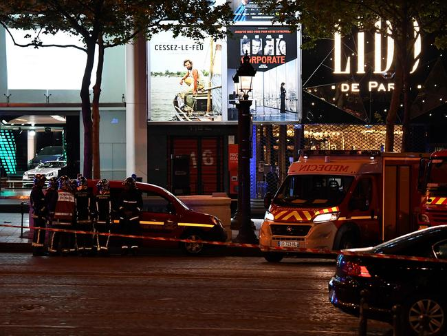 Firefighters and rescuers stand by the site of a shooting on the Champs Elysees in Paris.