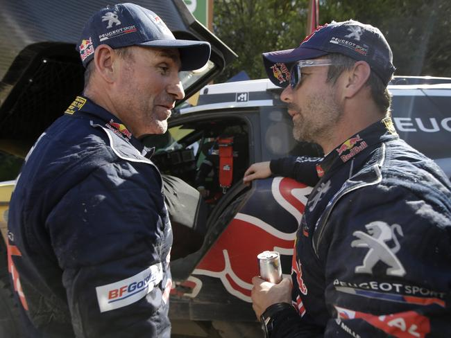Stephane Peterhansel, left, talks to Sebastien Loeb.