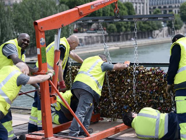 Moving on ... yellow-vested officials were out early on Monday morning on the city's iconic Pont des Arts, cutting off the padlocks. Picture: AFP/Stephane De Sakutin