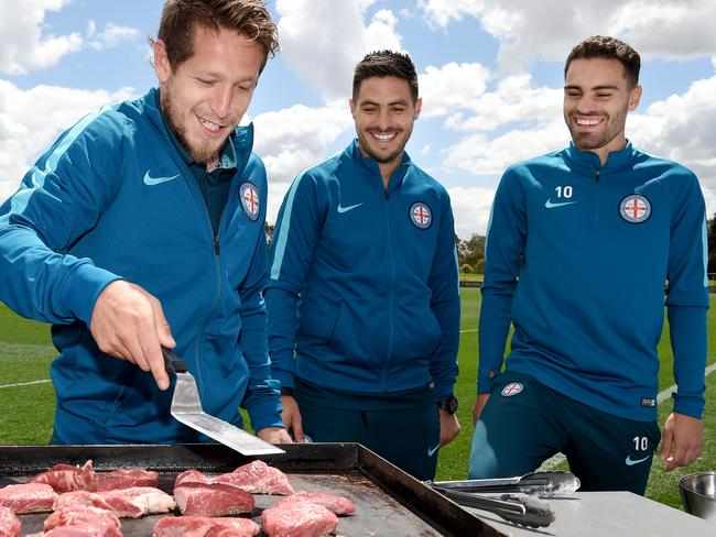 Fernando Brandan (left) tends the barbecue at training as Melbourne City teammates Bruno Fornaroli and Anthony Caceres look on.