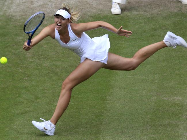 Maria Sharapova returns a shot at Wimbledon — and most importantly is wearing the right colour from head to toe.