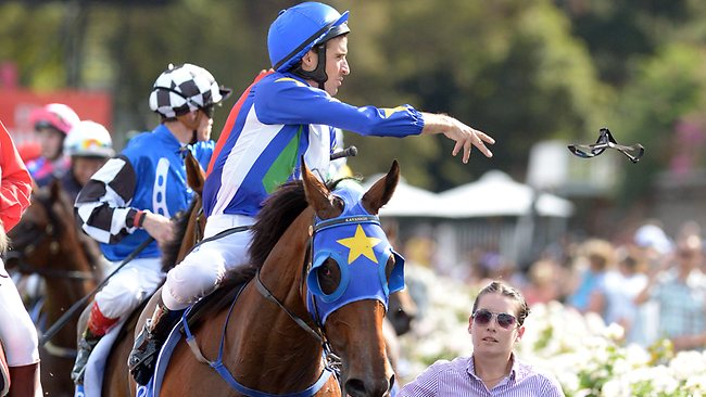 Jockey Michael Rodd throws his goggles into the crowd after Super Cool overhauled Fiveandahalfstar to clinch the Australian Cup. Picture: Wayne Ludbey