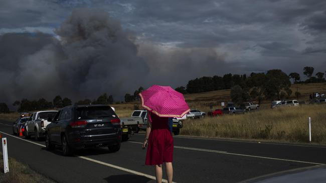 Genevieve Devin watches plumes of smoke as a fire approaches Hoskinstown. Picture: Sean Davey