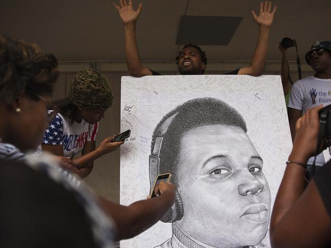 Not forgotten ... Mark Gaines holds up his hands as demonstrators autograph a sketch he drew of Michael Brown during a protest.