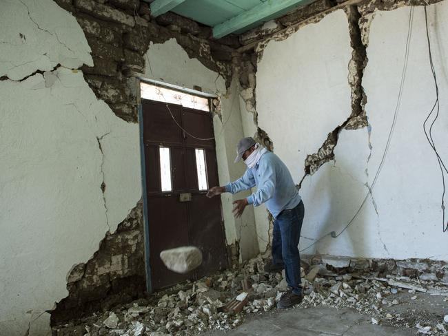 Damage ... a homeowner inspects the wreckage of his home in San Pedro. Picture: Oliver de Ros