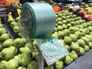 A plastic bag dispenser is seen in the fruit and vegetables area of a supermarket in Melbourne, Monday, July 17, 2017. Woolworths has announced plans to cease using plastic bags in its outlets. (AAP Image/Julian Smith) NO ARCHIVING