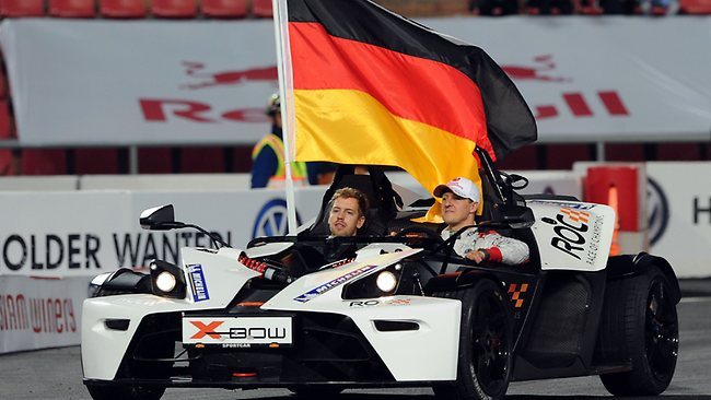 Seven times F1 world champion Michael Schumacher, right, looks out to the crowd next to 2012 F1 champion Sebastian Vettel after winning the Race of Champions.
