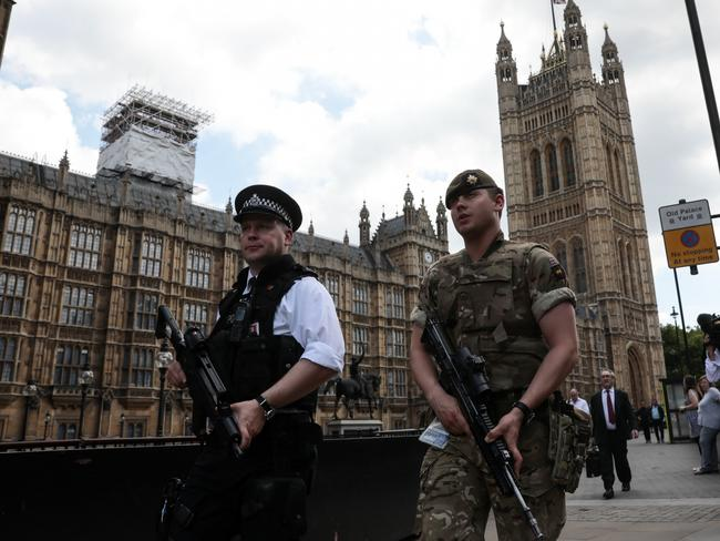 "A soldier and an armed police officer patrol outside the Palace of Westminster in London, U.K., on Wednesday, May 24, 2017. Soldiers were on patrol at the U.K. Parliament and prepared to guard major sporting events, as authorities rolled out the biggest homeland deployment of troops in decades to prevent an ""imminent"" terrorist attack. Photographer: Simon Dawson/Bloomberg"