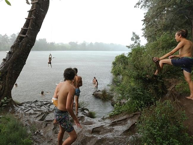 People cooling off in the Nepean river or on the rope swing at Tench Reserve, Jamisontown