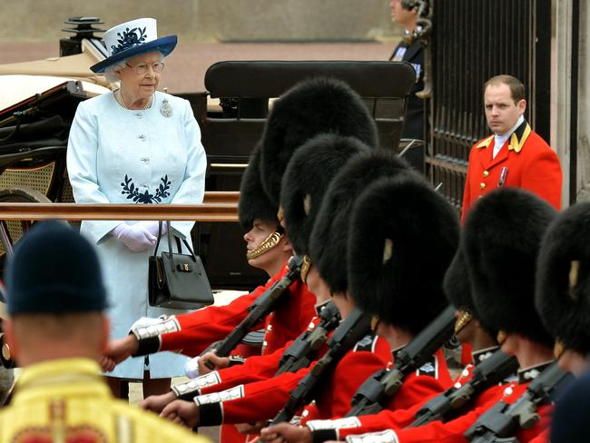 Queen Elizabeth II watches troops march past outside Buckingham Palace following Trooping the Colour parade back in 2014. Picture: John Stillwell/PA Wire