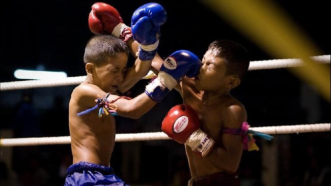 Young Muay Thai boxers fighting in the ringabout 410 kms northeast of Bangkok. The boxers aged between 8 to 25 compete in different categories. AFP PHOTO / Nicolas ASFOURI