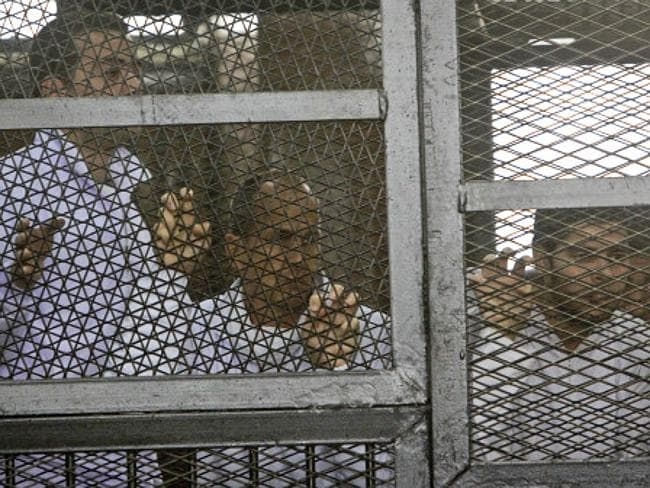 In the cage ... Al-Jazeera producer Baher Mohamed, left, and correspondent Peter Greste, centre, stand inside the defendants' cage in a courtroom during their trial on terror charges, along with several other defendants, in Cairo Picture: AP Photo/Mohammed Abu Zaid