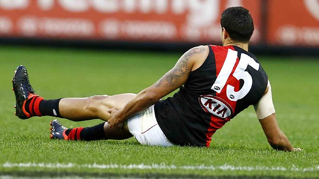 Courtenay Dempsey grabs his hamstring after trying to pick up a low ball during the first quarter. Picture: Michael Klein