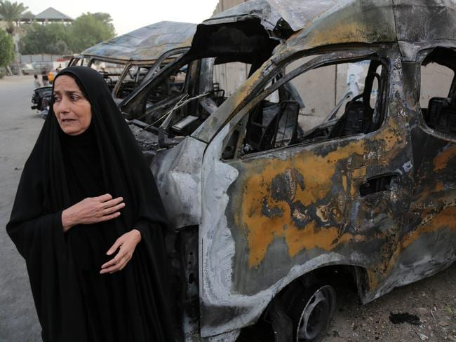 Shell-shocked ... a woman reacts to the carnage at the site of a car-bomb attack in the Shula neighbourhood of Baghdad yesterday. Picture: AP / Karim Kadim