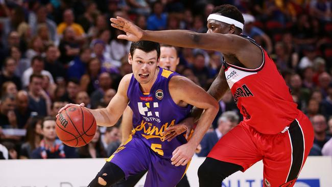 Jason Cadee drives past Kevin White of the Hawks during the round three NBL match.