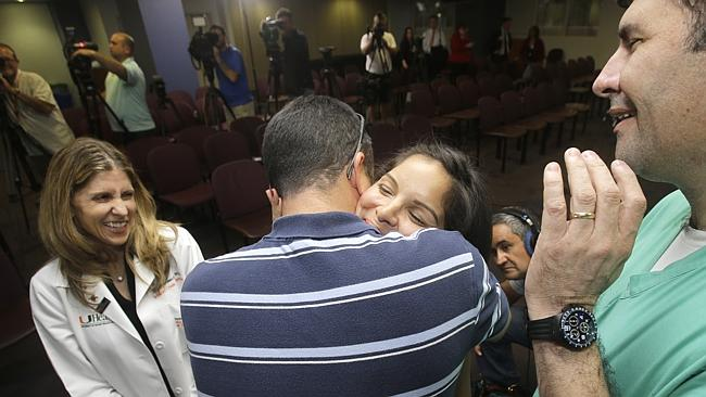 Pamela Rauseo, centre, is hugged by her husband Eduardo Luis Rauseo after a news conference at Holtz Center for Children, in Miami. Picture: AP