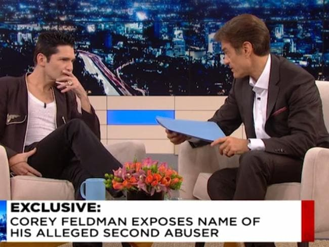 Corey Feldman appears on Dr Oz, who holds a blue envelope carrying the name of an alleged paedophile.